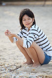 Teen women sitting on the beach and sea shell in h Royalty Free Stock Images