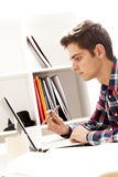 Teen working on computer. Teen working at laptop computer on home office desk Stock Images
