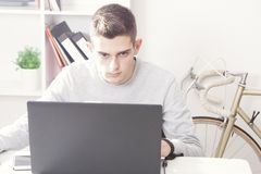Teen working on laptop. Teen boy working at laptop on home office desk Stock Photography