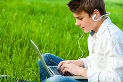 Teen working on laptop in green field. stock photography