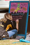 Teen Writes Popsicle Flavors On Chalkboard Before Event At Park Royalty Free Stock Images