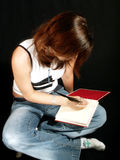 Teen writing diary. Teen girl writing in her diary stock photo