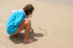 Teen writting on sand Stock Photo