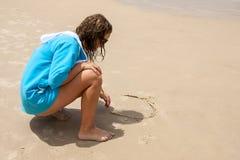 Teen writting on sand stock photo