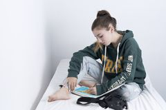 Teen 15 year old wearing a drawing. Sitting on her bed Royalty Free Stock Images