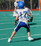 Teen Youth Football Player Ready to Catch. Ball on field during game Royalty Free Stock Photo