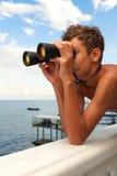 Un teenadger che guarda tramite il binocolo Fotografie Stock