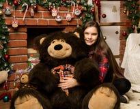 Teenag女孩是一件大大女用连杉衬裤在壁炉附近涉及圣诞节的容忍 图库摄影
