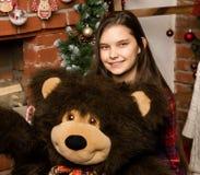 Teenag女孩是一件大大女用连杉衬裤在壁炉附近涉及圣诞节的容忍 免版税库存照片