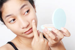 Teenage And Acne. Teenager checking her face for pimple in the mirror Stock Image
