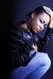 Teenage African American Girl, Kneeling and Looking Sexy. High Fashion Image of a Teenage African American / Black Girl, Wearing A Leather Jacket and Jeans Stock Photo