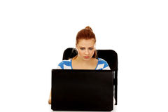 Teenage angry woman with laptop sitting behind the desk Royalty Free Stock Photos