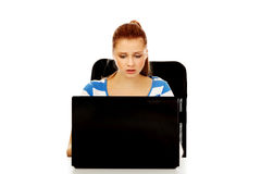 Teenage angry woman with laptop sitting behind the desk Royalty Free Stock Images
