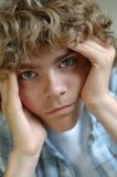 Teenage anguish. Upset teen with his hands propping his head; striking green eyes.  Extremely shallow depth of field Royalty Free Stock Image