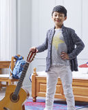 Teenage Asian boy holding guitar, posing & smiling in bedroom royalty free stock photography