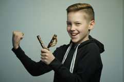 Teenage bad boy with slingshot and stylish haircut, studio shot. Portrait of a handsome teenage bad boy with slingshot and stylish haircut, softbox lighting stock image