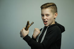 Teenage bad boy with slingshot and stylish haircut, studio shot Royalty Free Stock Images