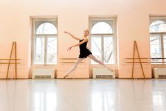 Teenage ballerina practicing ballet moves in large dancing studio stock photo