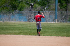 Teenage baseball shortstop from behind. American youth baseball player holding up hand Stock Images