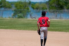 Teenage baseball shortstop on field with copy space. American youth baseball player running on field Royalty Free Stock Photos
