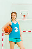 Teenage basketball player with ball under her arm Stock Photos
