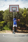 Teenage basketball player scoring while practicing at court. Against sky Royalty Free Stock Photography