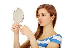 Teenage beautiful woman looking in a mirror Stock Photo