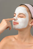 Teenage beauty girl touch nose facial mask Stock Photos