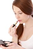 Teenage beauty putting lipstick on Stock Photography