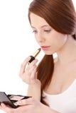 Teenage beauty putting lipstick on. Teenage gingerish girl putting lipstick on, looking herself in mirror Stock Photography