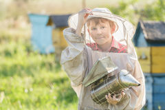 Teenage beekeeper using a smoker on bee yard Royalty Free Stock Photos