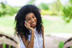 Teenage black girl using a mobile phone - African people. Smiling teenage black girl using a mobile phone  - African people Royalty Free Stock Image
