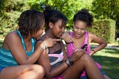 Teenage black girls using a phone,. Smiling teenage black girls using a phone at park Royalty Free Stock Photo