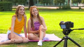 Teenage bloggers recording video by camera in park stock video