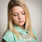 Teenage blond girl looking down stock photo