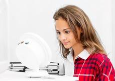 Teenage blond girl udergoes eye survey in ophthalmologic clinic. Teenage girl udergoes eye survey in ophthalmologic clinic with diagnostics device stock photos