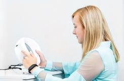 Teenage blond girl udergoes eye survey in ophthalmologic clinic. Holding diagnostics device stock images