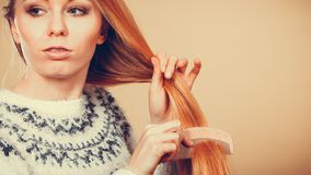 Teenage blonde girl brushing her hair with comb royalty free stock photos