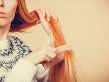 Teenage blonde girl brushing her hair with comb royalty free stock images