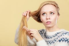 Teenage blonde girl brushing her hair with comb stock image