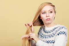 Teenage blonde girl brushing her hair with comb stock photo