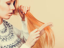 Teenage blonde girl brushing her hair with comb Royalty Free Stock Photo