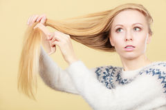 Teenage blonde girl brushing her hair with comb Stock Images