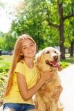 Teenage blonde girl with retriever dog otside. Beautiful blonde teenage girl portrait hugging her bellowed golden retriever dog in the park Stock Photos