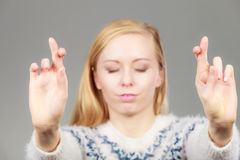 Teenage blonde woman making promise gesture. Gestures and signs concept. Teenage blonde woman making promise gesture with fingers crossed Royalty Free Stock Photography