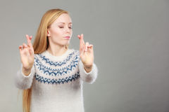 Teenage blonde woman making promise gesture. Gestures and signs concept. Teenage blonde woman making promise gesture with fingers crossed Royalty Free Stock Photos
