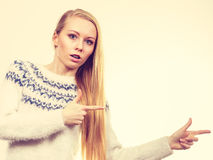 Teenage blonde woman pointing at copyspace Stock Images
