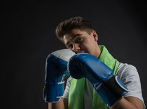 Teenage boxer posing with blue and white boxing gloves in a photographic studio. And with a green towel around his neck Stock Photos
