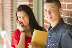 Teenage boy. A teenage boy looks at camera with a girl in the background on her phone Stock Images