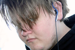 Teenage Boy 6. Teenage boy with hair over eyes and earphone in ear royalty free stock images